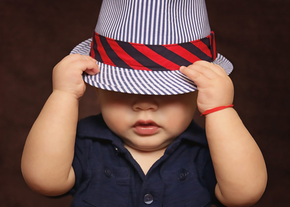 Picture a child reacting by holding hat when Mom is being firm to their demands.